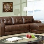 Elegant brown leather coated sectional with chaise in small size oval glass top table with black coat wood frame