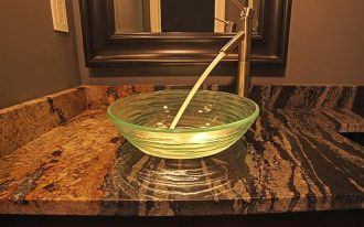 Glass vessel sink with steel faucet
