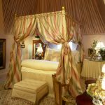 Gold-princess-Belle-bedroom-themed-with-large-and-white-bed-and-gold-canopy-bed-and-crystal-lamp-on-the-red-table-and-white-wall