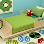 Green-modern-toddler-bed-by-kidkraft-with-storage-and-additional-seating-on-the-bench-and-neutral-and-natural-finishing