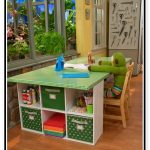 Green top desk for crafting with shelving unit at side of desk a wooden chair for kid