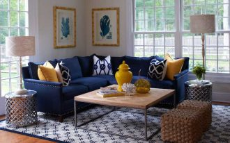 L shaped blue navy sectional sofa with accent pillows wood top coffee table with metal base a pair of crafted rattan ottoman chairs a pair of round top metal side tables large modern area rug