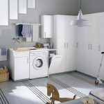 L shaped closet organizers in white a washer machine a dryer machine wall kit for hanging the clothes two rattan storage baskets a white pendant lamp