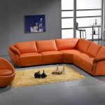 L shaped leather sectionl in orange color an orange bean chair light orange shaggy rug modern minimalist painting as wall art a pair of bar stools and small round table
