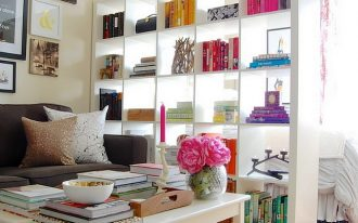 Large and high open booshelves room separator idea in white color that divides a bedroom and conversation room