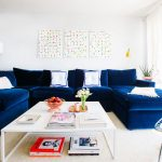 Large velvet blue navy sectional with chaise and white throw pillows an oversized white coffee table large white area rug for living room