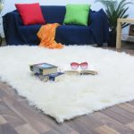 Large white fluffy rug a sofa with bright green and red throw pillows