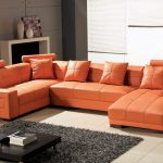 Larger orange leather sectional with single chaise and orange throw pillows a low profile coffee table in black coat grey wool rug a modern white console for displaying some ceramic vase ornaments