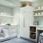 Laundry room cabinetry in white and big shelving units two rattan storage boxes