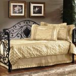 Light cream bedding idea for black coated metal daybed three gold toned pillows