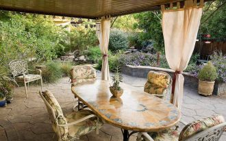 Table and chairs in garden room with privacy curtains, outdoor stone patio, California drought tolerant garden