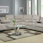 Light grey microfiber reclining sectional idea minimalist round glass coffee table with metal base larger wall niche for displaying some decorative items some wall art pieces light and deep grey rug