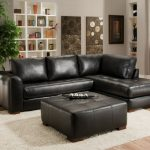 Luxurious and classy black leather sectional with chaise in small size a black leather ottoman with wood legs as the  coffee table pure white wool rug a round glass side table with metal base