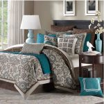 Luxurious and comfy bedding in teal and brown color schemes a lot of pillows with similar color schemes dark coated wood side table with drawer and single shelf underneath thiny grey rug