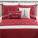 Luxurious and cozy white and red comforter a pair of bedside tables a classic table lamp a bed furniture with black metal headboard