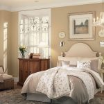 Luxurious and warm color options for a vintage bedroom decor idea  light beige wall paint a bed frame with white headboard beige and white comforter beige and white pillowcases a rattan chair