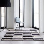 Modern area rug with black white and grey lines a simple and elegant chair with tiny metal legs a standing lamp with huge black cap