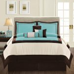 Modern bed frame with light grey headboard and modern patterned bedding and pillows in brown and teal colors a bedside table with a table lamp and under shelf