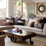Modern-coffee-table-with-wheels-and-rustic-design-and-soft-beige-sofa-with-colors-pillow-and-books-and-ashtray-and-wooden-floor-surrounded-with-white-wall-and-white-window-and-door