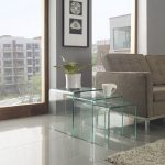 Modern living room with grey sofa grey shaggy area rug three series of clear nesting side tables with a white vase plus decorative plant and a white cup