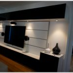 Modern minimalist entertainment center IKEA idea with wall mounted TV set under cabinet light fixtures a set of audio system some decorative vases in black and white