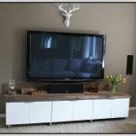 Modern white TV console with wood top transparent glass vase with beautiful flower a decorative white deer head replica made from wood a pair of wall mounted audio system
