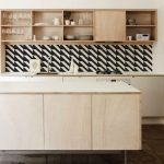 Monochromotic wallpaper for backsplash in simple and small kitchen  unfinished wall mounted wooden open shelves for displaying dishware collection  a kitchen island with white top