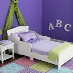 Nantucket-white-toddler--bed-by-kidkraft-from-strong-and-durabe-rubber-wood-with-smooth-white-lines-and-regular-crib-mattress-surrounded-with-purple-color-wall