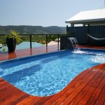 Natural View Of Beautiful Pool With Wooden Deck And Waterfall