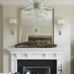 Nickel framed mirror over the fireplace mantel a pair of  wall light fixtures a decorative lamp