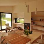 Open Room Design Of Warm Living Room And Kitchen With Electric Fireplace Book Shelf White Furniture And Elegant Lamp