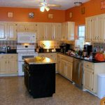 Orange KItchen Wall Paint With Wood Kitchen Set And Table In The Middle
