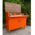 Orange painted wooden bar cabinetry in vintage style