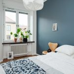 Orange-series7-chair-beside-large-white-bed-and-blue-wall-with-two-windows-on-white-wall-and-white-door-also-vases-and-flowers-near-windows