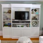 Pure white TV cabinet with open shelves for displaying the picture frames some decorative items and media players