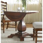 Round drop leaf table with single leaf made from solid wood a pair of wood chairs with grey cushion