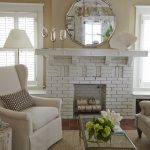 Round mirror with stainless steel frame idea over white brick fireplace a white standing lamp an armchair with smaller throw pillow square glass coffee table with stainless steel frame