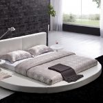 Round white low profile bed furniture with white leather headboard white mattress with grey bedding and grey pillows built in white round bedside table