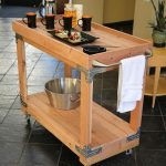 Rustic wooden bar cart with wheels and metal pin for each edge of bar cart