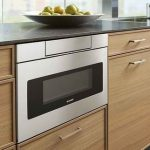 Silver-Sharp-24inch-microwave-drawer-SMD2470AS-with-hidden-control-installed-in-beige-cabinet-and-under-counter-near-glass-window-also-apples-on-a-plate