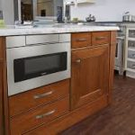 Silver-Sharp-24inch-microwave-drawer-SMD2470AS-with-hidden-control-installed-in-brown-wooden-cabinet-and-under-counter-also-brown-floor-and-white-wall
