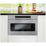 Silver-sharp-24inch-microwave-drawer-oven-SMD2470ASS-with-hidden-control-and-in-white-cabinet-also-under-counter-near-glass-window-adorned-with-small-soft-brown-pot-and-green-plant