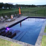 Simple Rectangular Pool With Pool Furniture And Fireplace