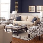 Simple living room idea by NYC with  cream sofa plus dark throw pillows anda pair of single sofa a coffee table ottoman with under shelf a pair of table lamps a pair of black side tables