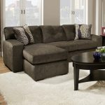 Simple small sectional with chaise in darker grey a pair of pillows with modern pattern black wood coffee table in oval shape white wool rug