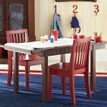 Simple wood craft table with a paper roller a pair of red painted wooden chairs large blue rug with red and white frame