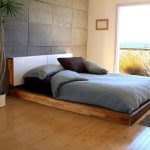 Simple wood king platform bed frame with minimalist white headboard grey wool bedroom rug a white pot for a decorative plant