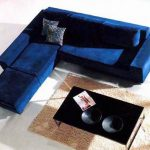 Small L-shaped sectional with chaise in blue navy a pair of decorative pillows black coffee table medium sized cream rug rug for living room