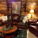 Small Rustic Living Room With Small Sofa Round Wooden Table Wood Wall Green Rug And Double Lamps