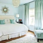 Soft and smooth white fluffy bedroom rug turquoise reading chair a king bed furniture with white bedding and turquoise pillows a crystal pendant lamp floor to ceiling window curtain